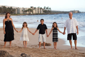 family and siblings hold hands on beach